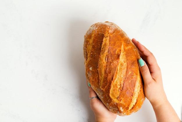 Pane sano naturale appena sfornato fatto in casa nelle mani di una donna su uno sfondo di marmo grigio chiaro.