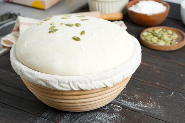 Pasta di lievito appena preparata fatta in casa in un cestino per cottura con semi di zucca su legno scuro.