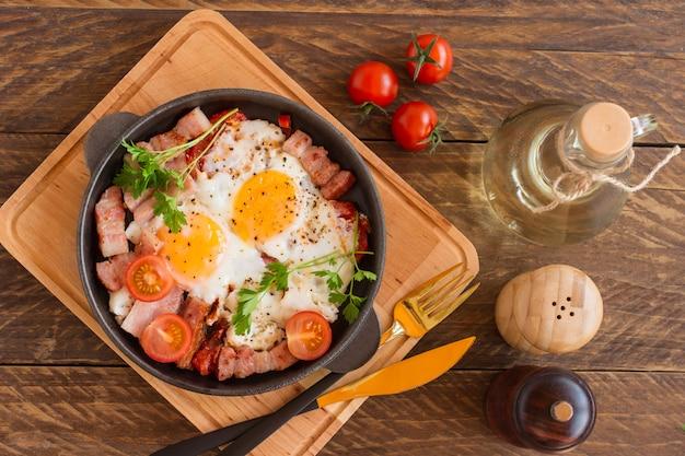 Uova fritte fatte in casa con pancetta e pomodori in padella su fondo di legno. colazione classica. vista dall'alto.