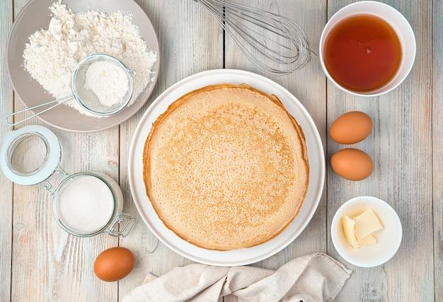 Frittelle fatte in casa, fritte su un piatto e ingredienti per cucinarle su una superficie leggera. vista dall'alto, con spazio per scrivere. il concetto di cucina, ricette, mardi gras.