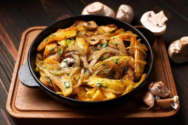 Patate fritte fatte in casa, con cipolle, funghi e aglio, in padella, su una tavola di legno
