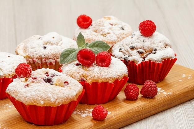 Muffin alla frutta fatti in casa cosparsi di zucchero a velo e lamponi freschi su tagliere di legno. dolci e pasticcini natalizi.