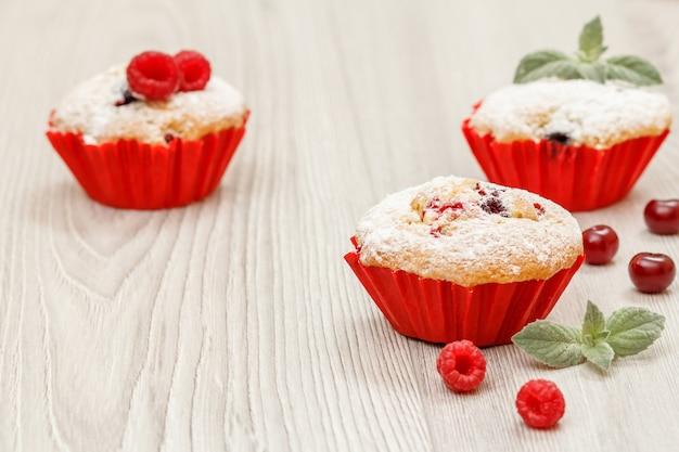 Muffin alla frutta fatti in casa cosparsi di zucchero a velo e lamponi freschi sulla scrivania in legno. dolci e pasticcini natalizi.