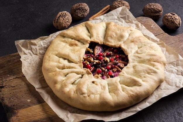 Torta galette fatta in casa con mele, bacche di sambuco e noci decorata con mirtilli rossi freschi sulla vecchia tavola di legno