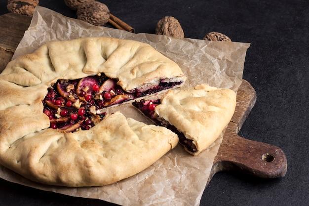Galette fatta in casa con mele, bacche di sambuco e noci decorate con cowberry fresco su superficie scura rustica