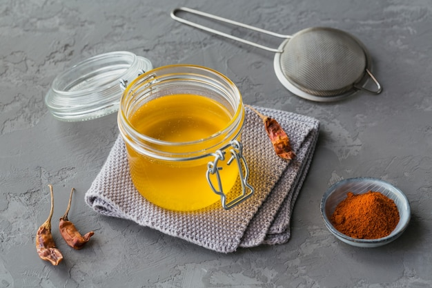 Ghee fatto in casa o burro chiarificato in un barattolo, peperoncino e paprika in polvere su cemento grigio.