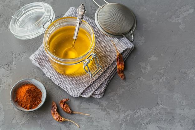 Ghee fatto in casa o burro chiarificato in un barattolo, peperoncino e paprika in polvere su grigio.