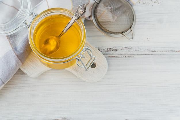 Ghee casalingo o burro chiarificato in un vaso sulla tavola di legno bianca.