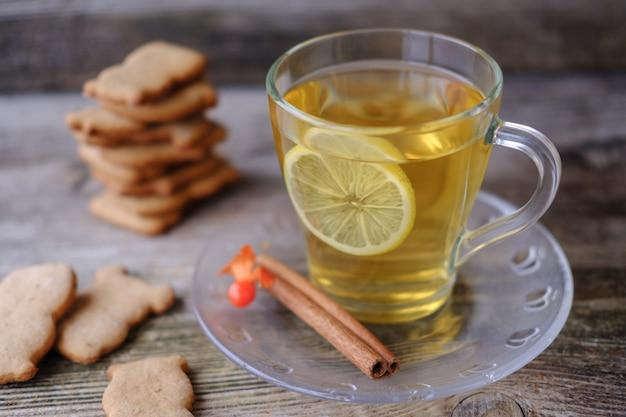Biscotti fatti in casa allo zenzero a forma di animali, tè verde al limone in una tazza di vetro, cannella e physalis sul vecchio tavolo in legno