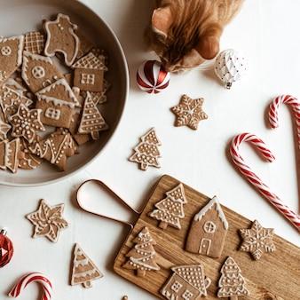 Biscotti allo zenzero fatti in casa stelle, abeti, case sul tagliere di legno, caramelle stick e bellissimo simpatico gatto rosso su bianco