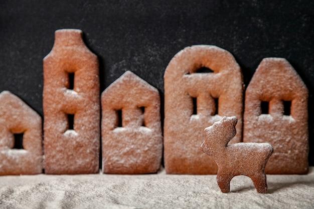 Città di pan di zenzero fatta in casa in fila con cervi di natale cosparsi di zucchero a velo su sfondo nero.