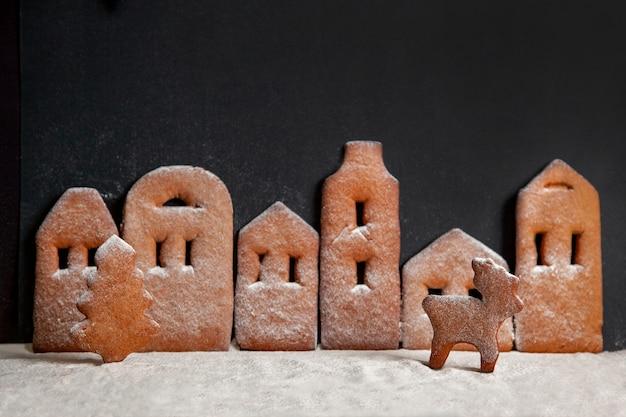 Città di panpepato fatta in casa, in piedi in fila con un albero di natale e cervi cosparsi di zucchero a velo su sfondo nero