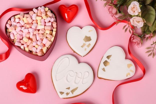 Pan di zenzero fatti in casa a forma di cuori e una scatola di marshmallow per il giorno di san valentino si trova su uno sfondo rosa, vista dall'alto, primo piano