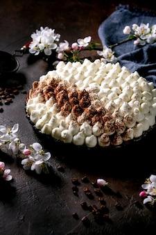 Tiramisù fatto in casa senza glutine tradizionale dolce italiano cosparso di cacao in polvere decorato con melo in fiore, tovagliolo in tessuto blu e chicchi di caffè su superficie scura.