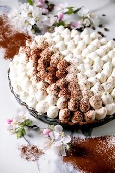 Tiramisù fatto in casa senza glutine tradizionale dolce italiano cosparso di cacao in polvere decorato con melo in fiore e chicchi di caffè su sfondo di marmo bianco.