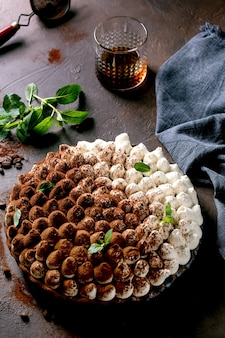 Tiramisù fatto in casa senza glutine tradizionale dolce italiano cosparso di cacao in polvere decorato con foglie di menta, bicchiere di whisky, tovagliolo in tessuto blu e chicchi di caffè su sfondo scuro.