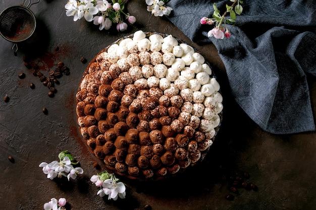 Tiramisù fatto in casa senza glutine tradizionale dolce italiano cosparso di cacao in polvere con melo in fiore, tovagliolo in tessuto blu e chicchi di caffè su superficie scura. vista dall'alto, posizione piatta