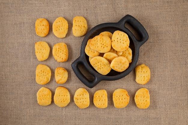 Biscotto senza glutine fatto in casa nel piatto di legno i biscotti si trovano sulle file della tela da imballaggio