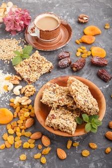 Granola fatta in casa da fiocchi d'avena, datteri, albicocche secche, uvetta, noci con una tazza di caffè su uno sfondo di cemento nero. vista laterale.