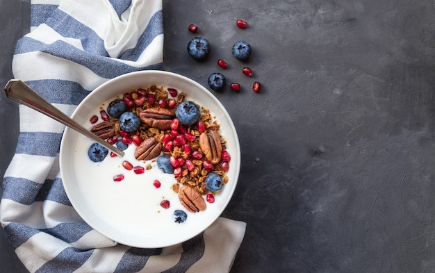 Muesli fatti in casa con semi di melograno mirtilli noci pecan e yogurt su sfondo grigio cemento