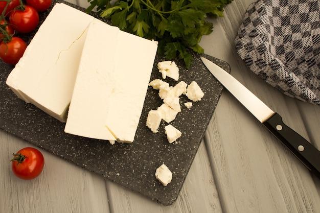 Feta di formaggio greco casalingo sul tagliere grigio
