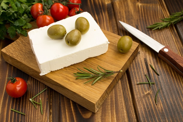 Feta di formaggio greco fatto in casa con olive verdi e ciliegia sul tagliere di legno