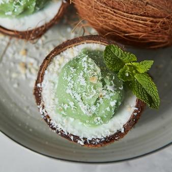 Gelato verde fatto in casa in un guscio di noce di cocco, foglia di menta su un piatto in ceramica grigia su un grigio chiaro. vista dall'alto. concetto vegetariano di mangiare dietetico