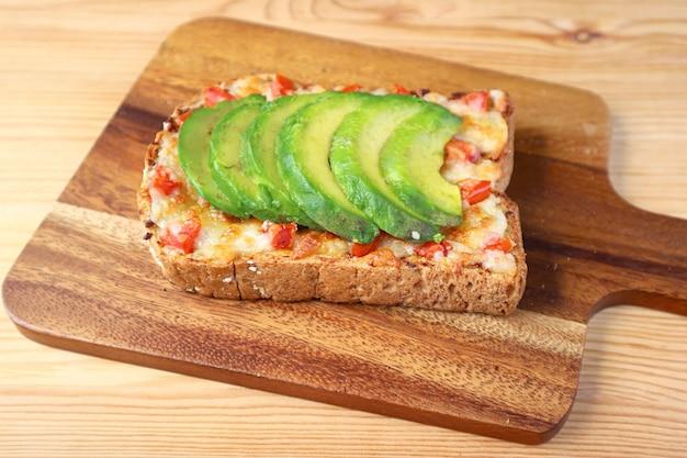 Toast al formaggio grigliato fatto in casa condita con pomodoro e avocado a fette su tagliere di legno