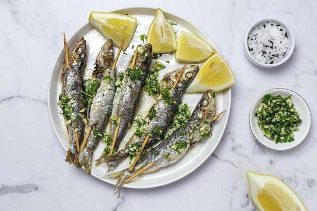 Sardine alla griglia fatte in casa con aglio, olio d'oliva, prezzemolo fresco e limone.concetto di cibo sano
