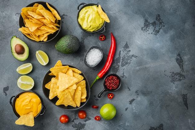 Guacamole fatto in casa e salsa di formaggio con nachos, su sfondo grigio, vista dall'alto o piatto con copia spazio per il testo