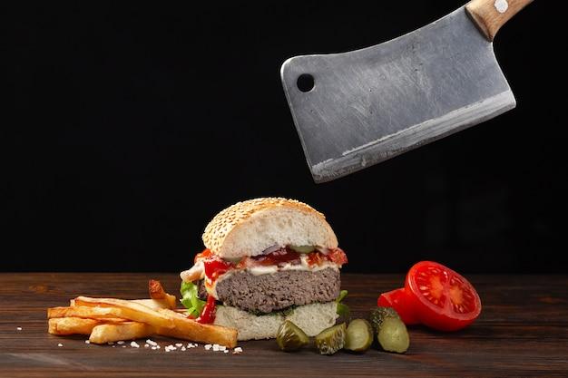Hamburger fatto in casa tagliato a metà primo piano con manzo, pomodoro, lattuga, formaggio e patatine fritte sul tavolo di legno. mannaia in mano. fastfood su sfondo scuro.