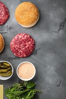Hamburger fatto in casa. polpette di manzo crudo, panini al sesamo con altri ingredienti, su sfondo di pietra grigia, vista dall'alto piatta, con spazio di copia per il testo