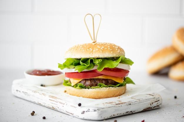 Hamburger fatti in casa con ketchup e spezie su una lavagna bianca