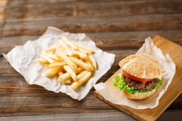 Hamburger fatti in casa e patatine fritte sul tavolo di legno