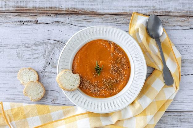 Crema di zucca casalinga e sana con pane dall'alto sulla tavola di legno. lay piatto