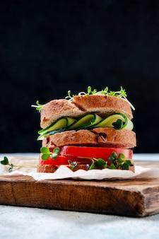 Panino sano fatto in casa con insalata di crescione di pane integrale, cetriolo, pomodoro e micro erbe su tavola di legno.