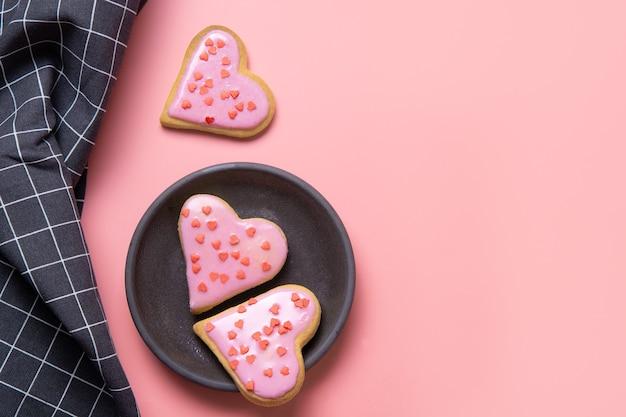 Biscotti fatti in casa a forma di cuore sulla tavola bianca.