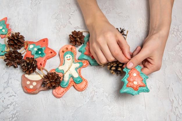 Decorazione domestica fatta in casa per natale. le mani dei bambini stanno tenendo una ghirlanda fatta in casa. gli uomini di pan di zenzero sono fatti di pasta salata, coni.