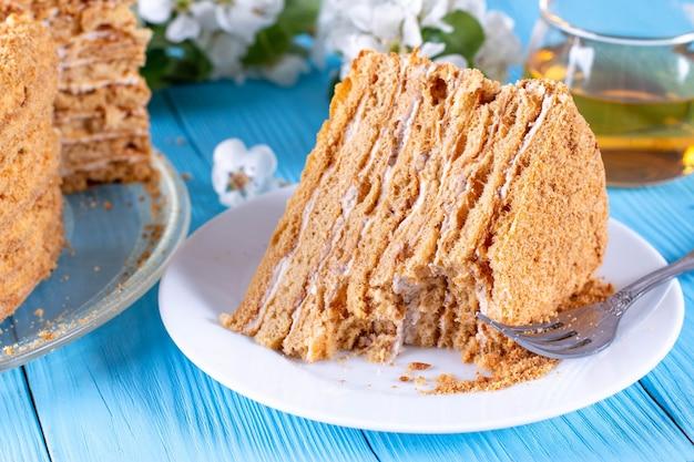 Torta al miele fatta in casa con panna acida su un tavolo di legno blu