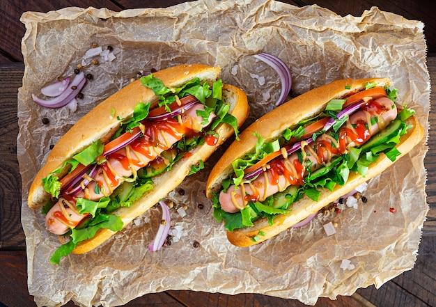 Hot dog fatti in casa con salsiccia su sfondo di legno