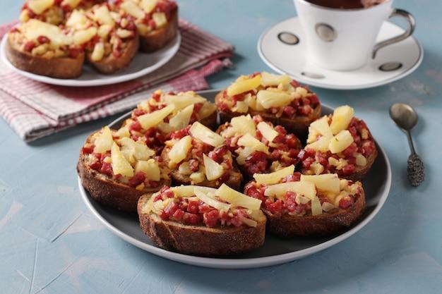 Panini caldi fatti in casa con salsiccia, formaggio e ananas su sfondo blu. deliziosa colazione o merenda.