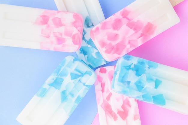 Bastoncini di gelato fatti in casa, ghiaccioli, pop di ghiaccio o pop di congelatore su sfondo blu e rosa colori pastello