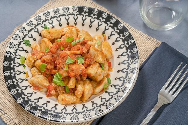 Gnocchi italiani fatti in casa con salsa rossa serviti su un piatto decorato.