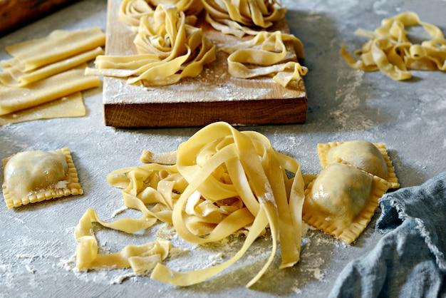 Pasta italiana fatta in casa, ravioli, fettuccine, tagliatelle su una tavola di legno e su uno sfondo blu.