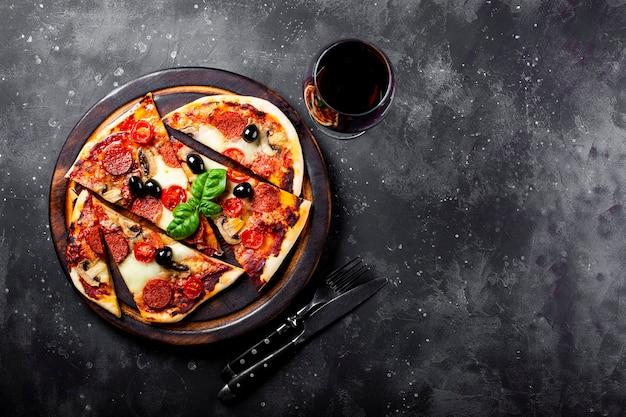Pizza italiana fatta in casa con mozzarella, salame piccante, olive e basilico e un bicchiere di vino rosso