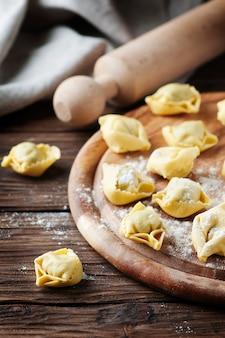 Tortellini tradizionali italiani fatti in casa sul tavolo di legno