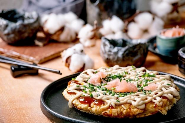 Frittella di cavolo okonomiyaki giapponese fast food fatta in casa con cipolla, zenzero sottaceto, salsa mayo su piastra in ceramica nera. bacchette, teiera, cotone, ingredienti sopra .. lay piatto