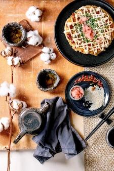 Frittella di cavolo okonomiyaki giapponese fast food fatta in casa con cipolla, zenzero sottaceto, salsa mayo su piastra in ceramica nera. bacchette, teiera, cotone, ingredienti sopra. tabella delle texture. lay piatto