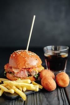 Hamburger succosi fatti in casa su tavola di legno, palline di formaggio.