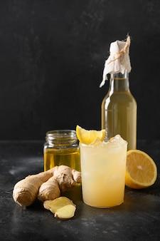 Kombucha fatta in casa sana e gustosa bevanda in bottiglia e bicchiere con menta guarnita al limone